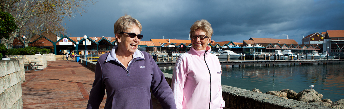 Two ladies smiling and walking by a harbour enjoying life