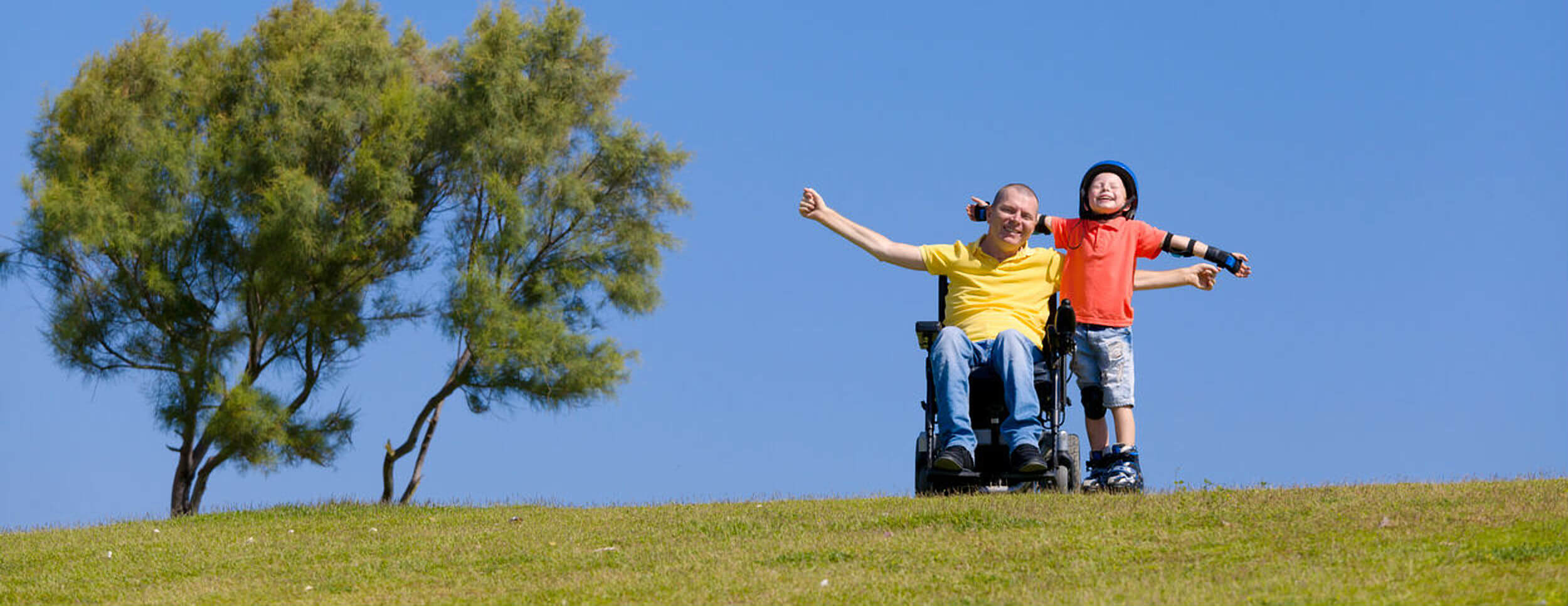 Happy man in a wheelchair with a young boy on a hill in the sun