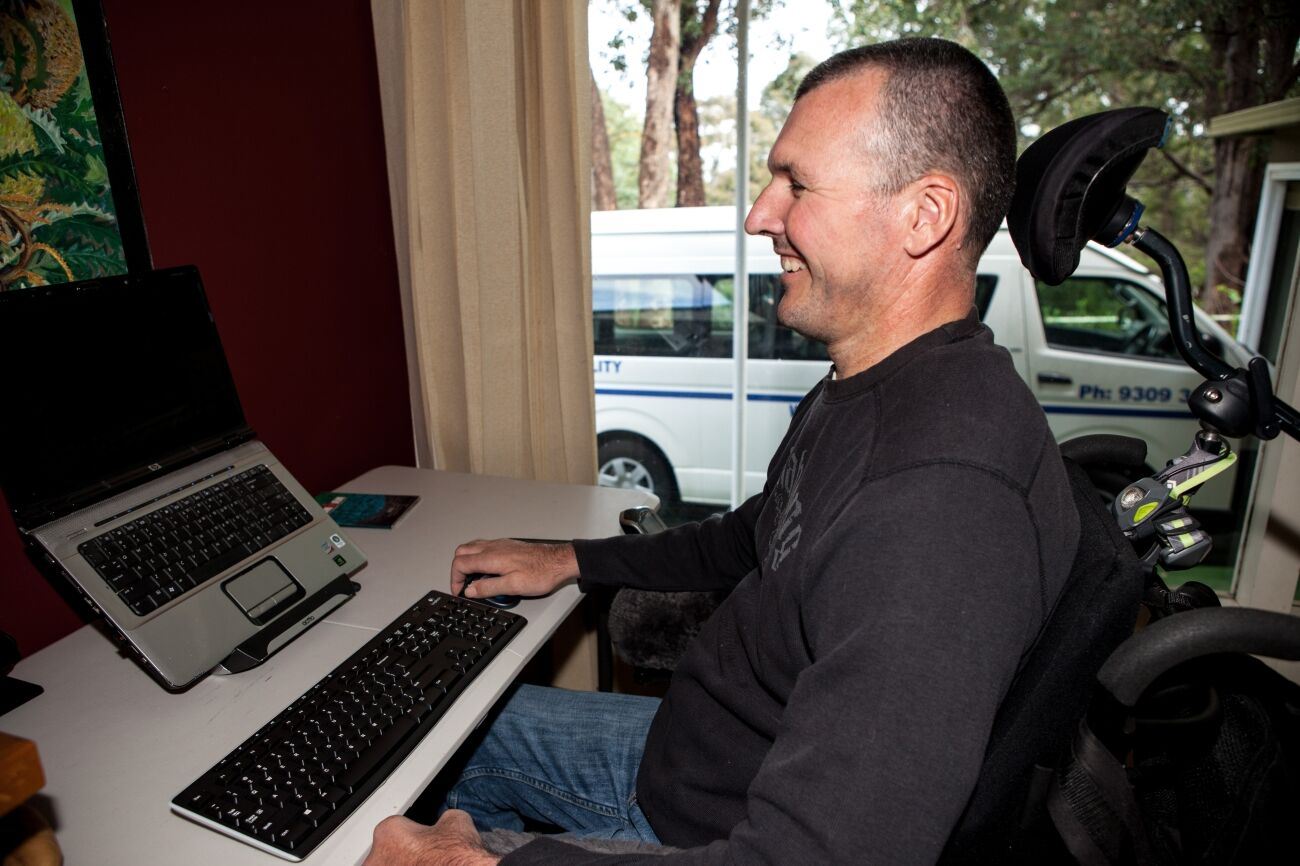 Smiling man looking at a computer sitting comfortably in a wheel chair